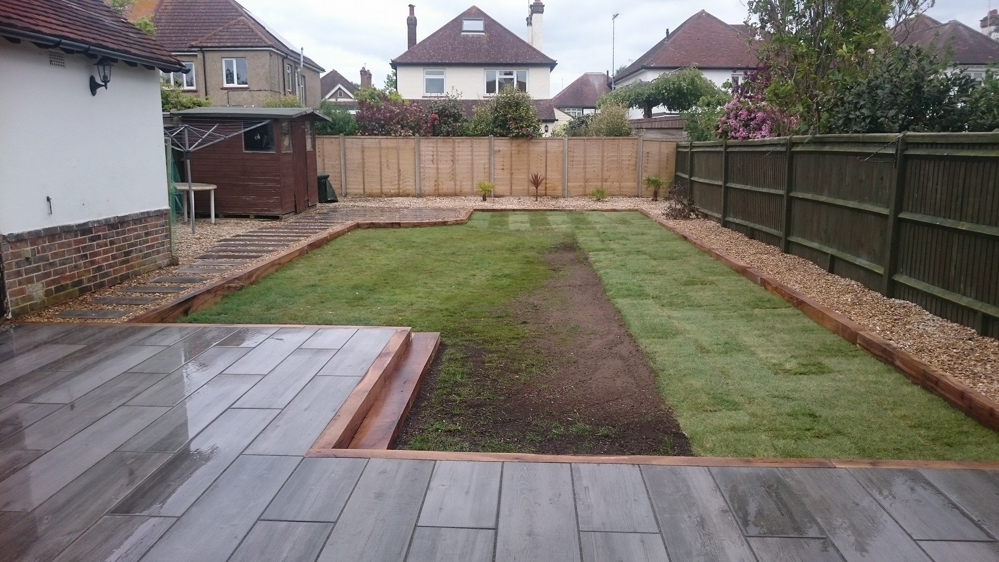 Wood effect patio with wooden border and porcelain 'stepping stones'.