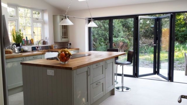 Indoor outdoor kitchen with island and bifold doors, featuring Valverdi tiles.
